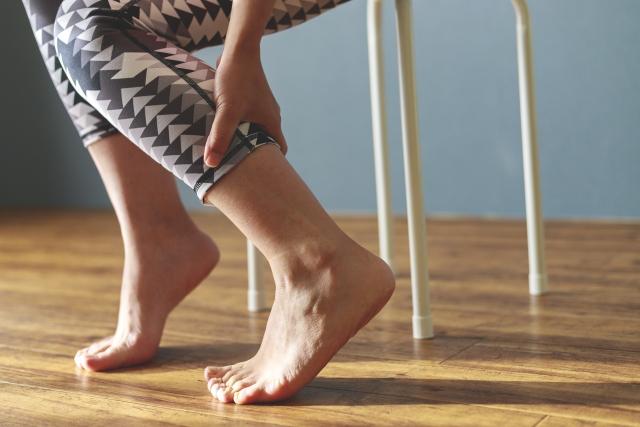 足首を痛がる女性