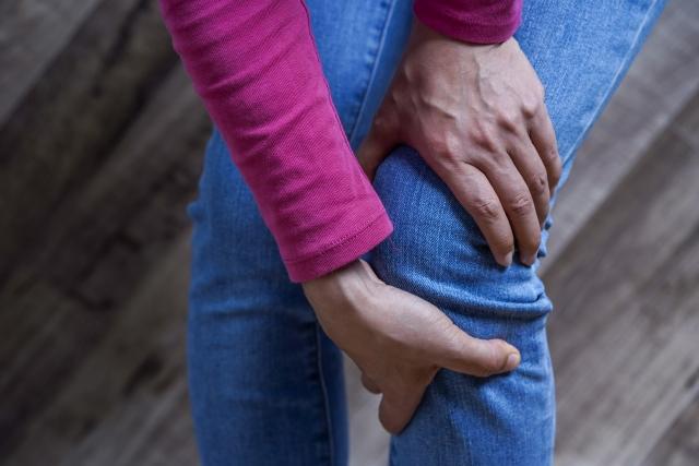膝を痛がる女性